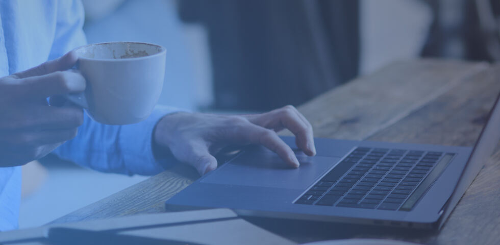 image of a person on a laptop with a cup of coffee